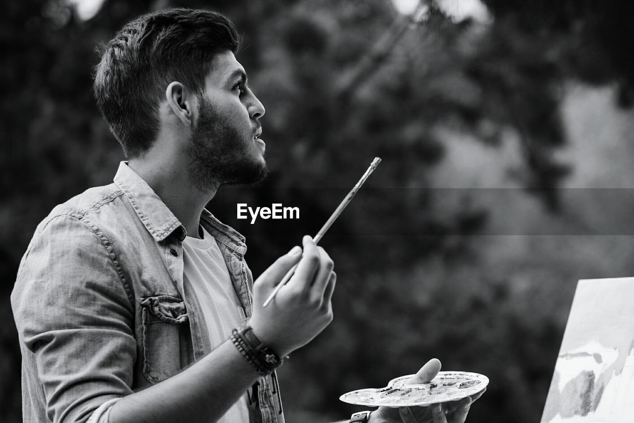 Painter Looking Up While Holding Paintbrush And Palette