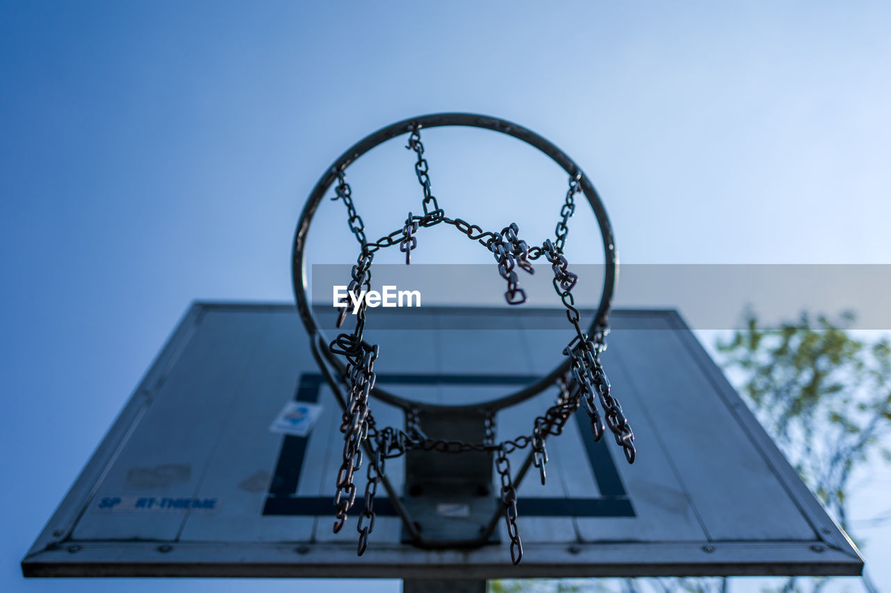 sky, low angle view, basketball hoop, metal, no people, basketball - sport, day, blue, clear sky, nature, sport, net - sports equipment, focus on foreground, outdoors, shape, architecture, design, close-up, circle, built structure, directly below