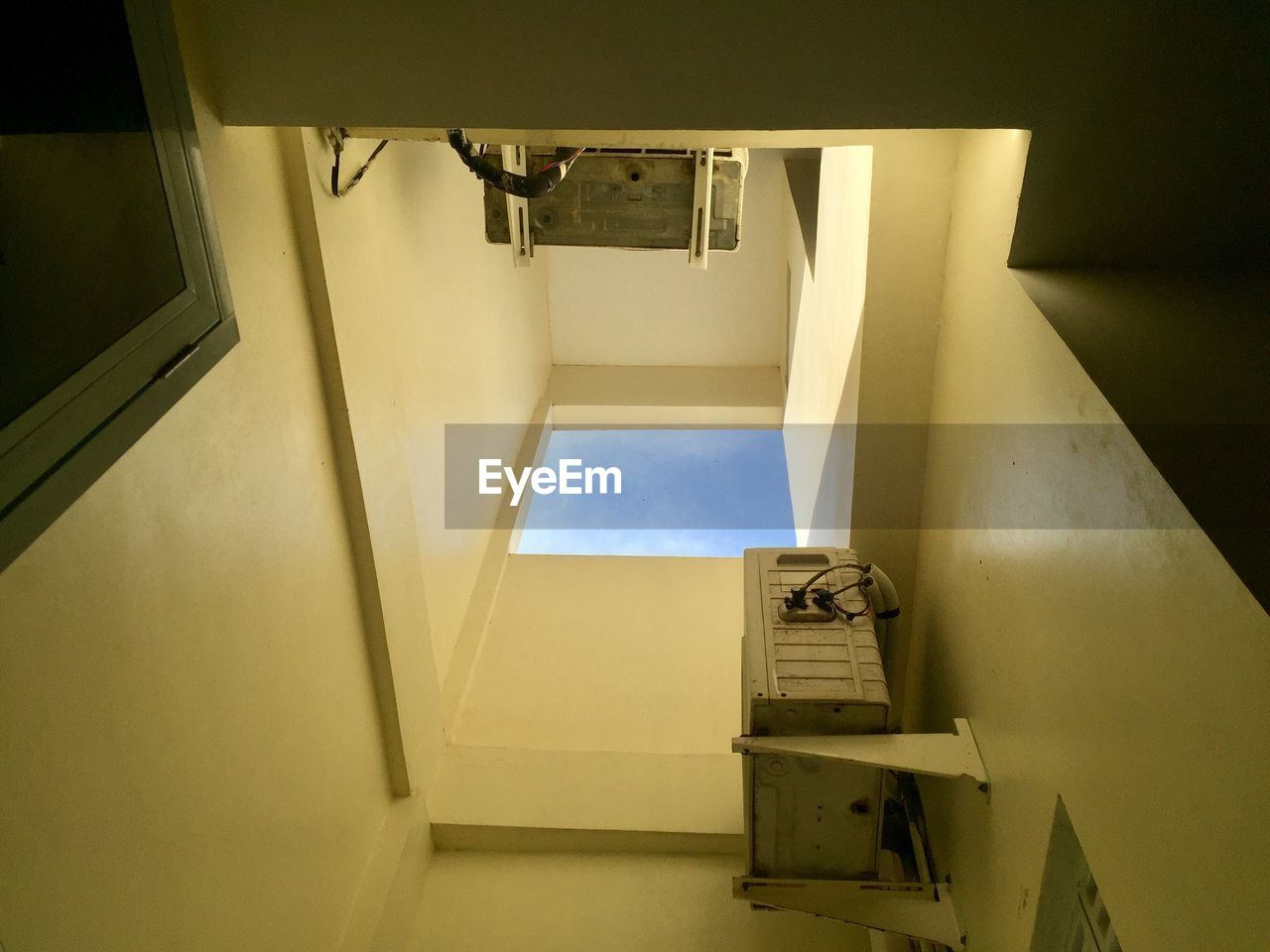 indoors, architecture, wall - building feature, no people, home interior, building, staircase, empty, built structure, door, high angle view, open, entrance, security, domestic room, sunlight, absence, technology, railing, illuminated, directly below, ceiling