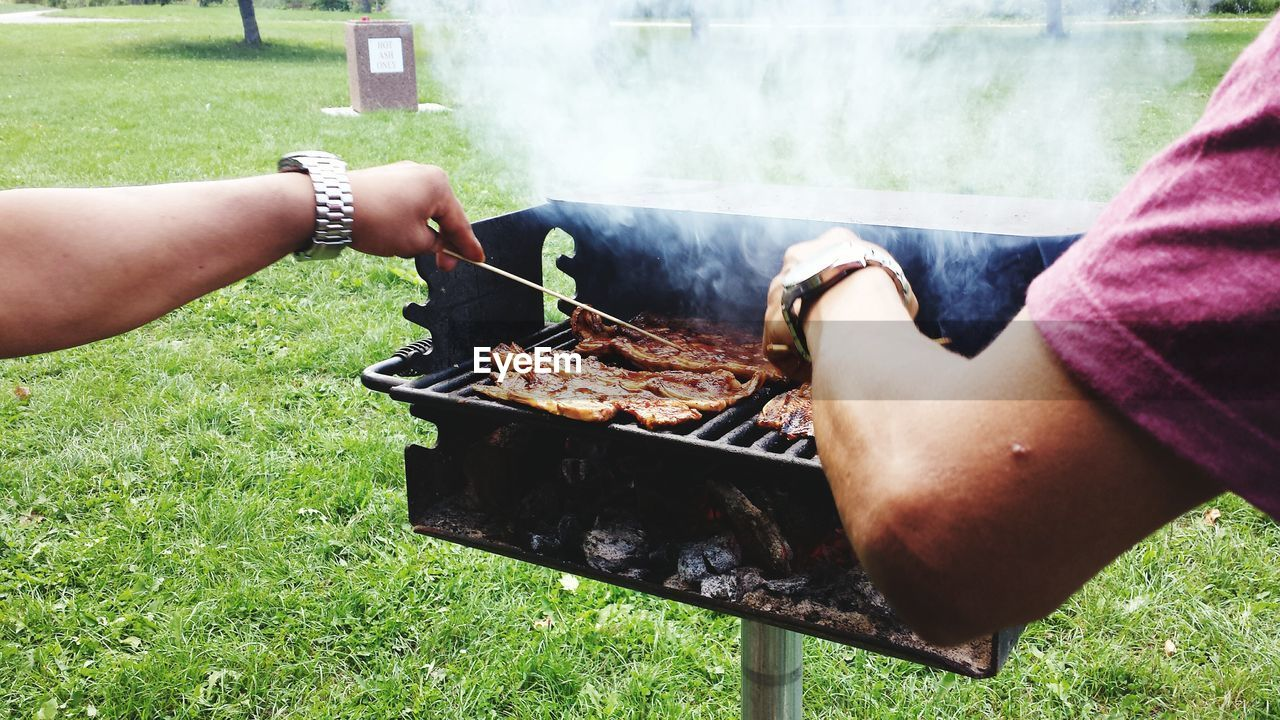 Cropped Image Of Men Barbecuing In Park
