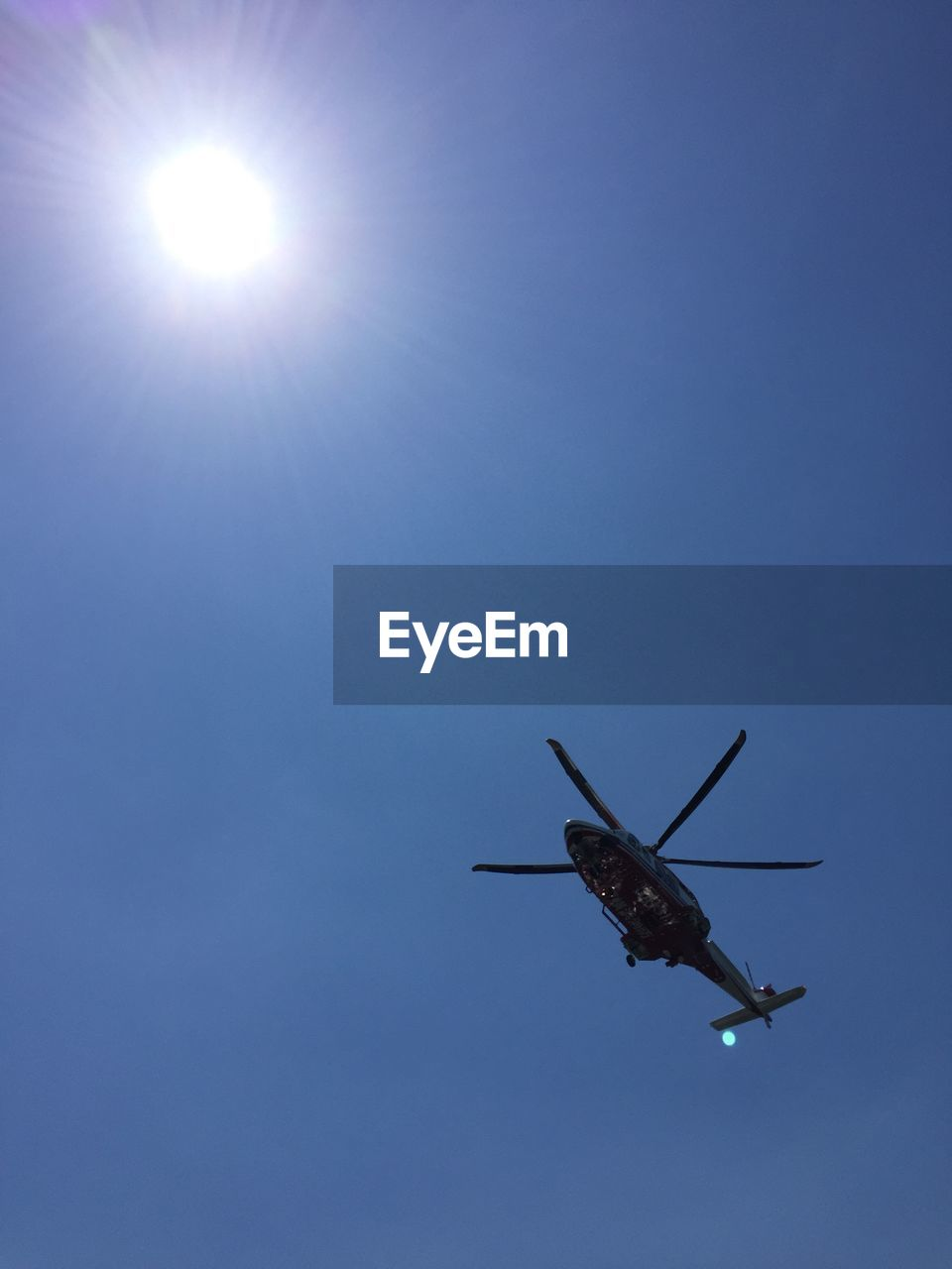 sky, low angle view, blue, flying, air vehicle, clear sky, mode of transportation, transportation, nature, mid-air, sunlight, helicopter, sun, no people, airplane, travel, sunny, copy space, day, sunbeam, outdoors, aerospace industry