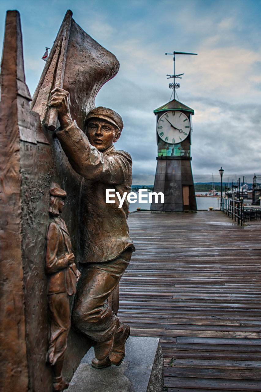 architecture, art and craft, sculpture, built structure, human representation, statue, sky, representation, male likeness, building exterior, cloud - sky, wood - material, creativity, day, no people, craft, travel destinations, nature, building, tower, government