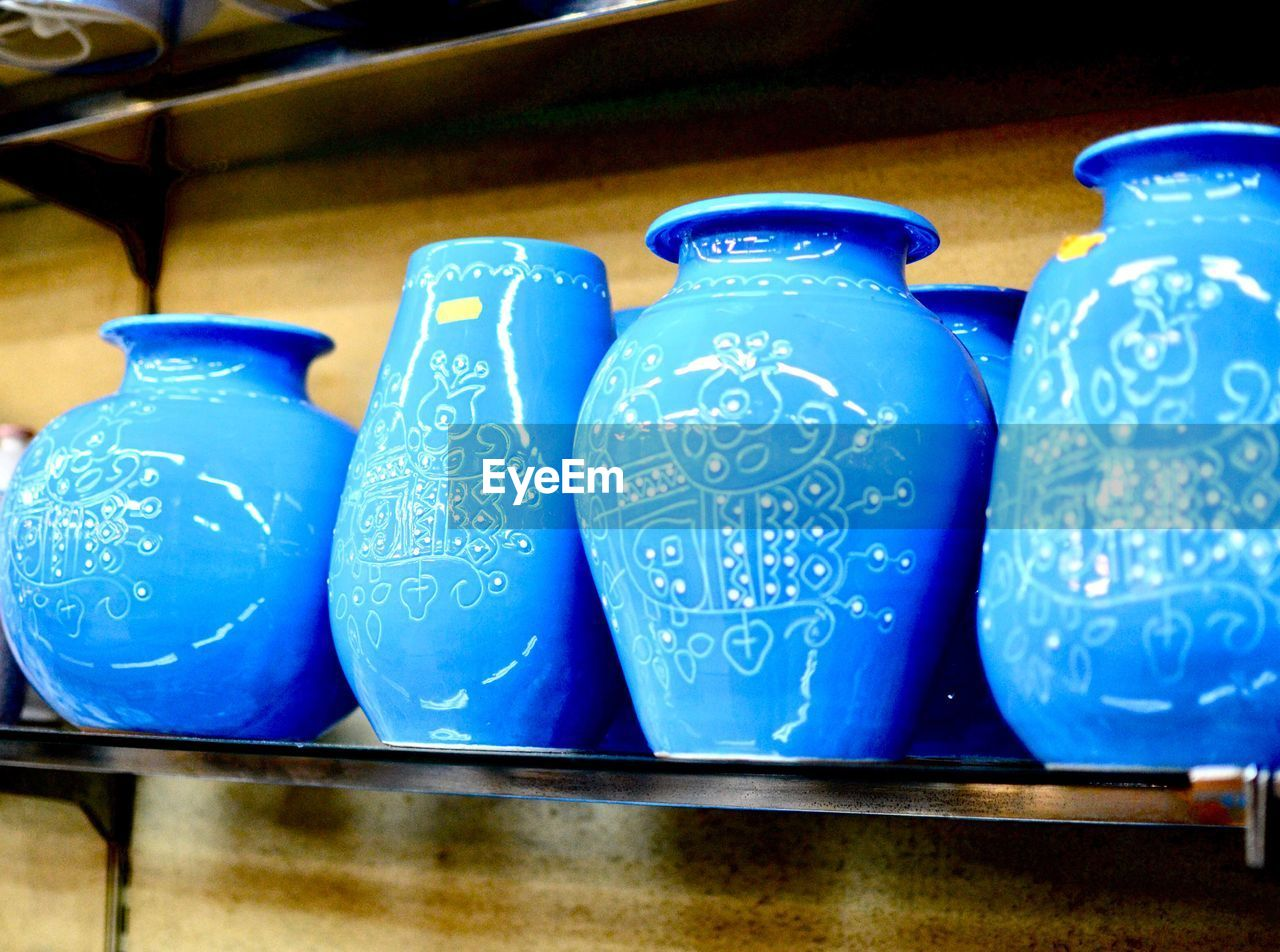 blue, no people, indoors, container, still life, close-up, side by side, ceramics, transparent, pattern, art and craft, arrangement, shelf, table, for sale, wood - material, retail, glass - material, craft, plastic