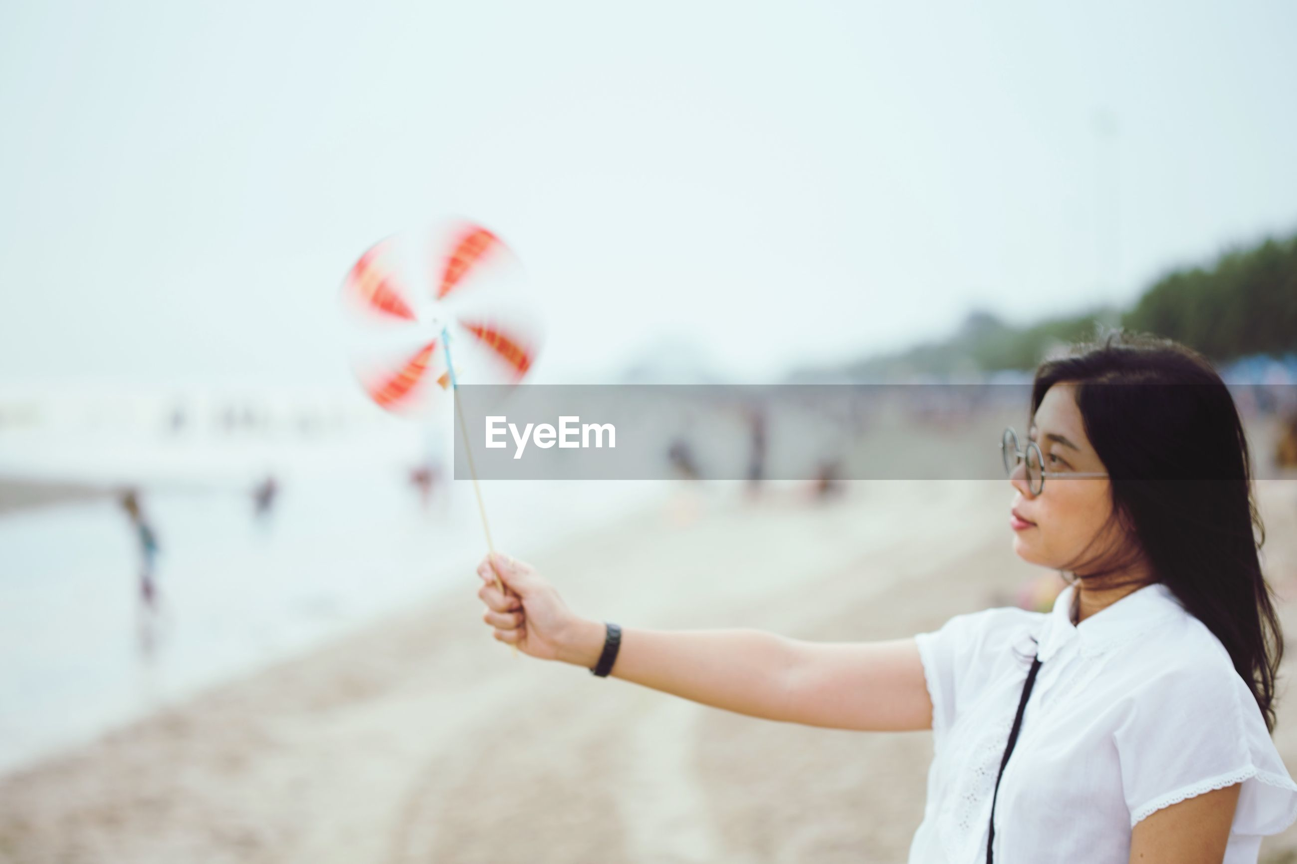 Woman holding pinwheel while standing at beach against sky