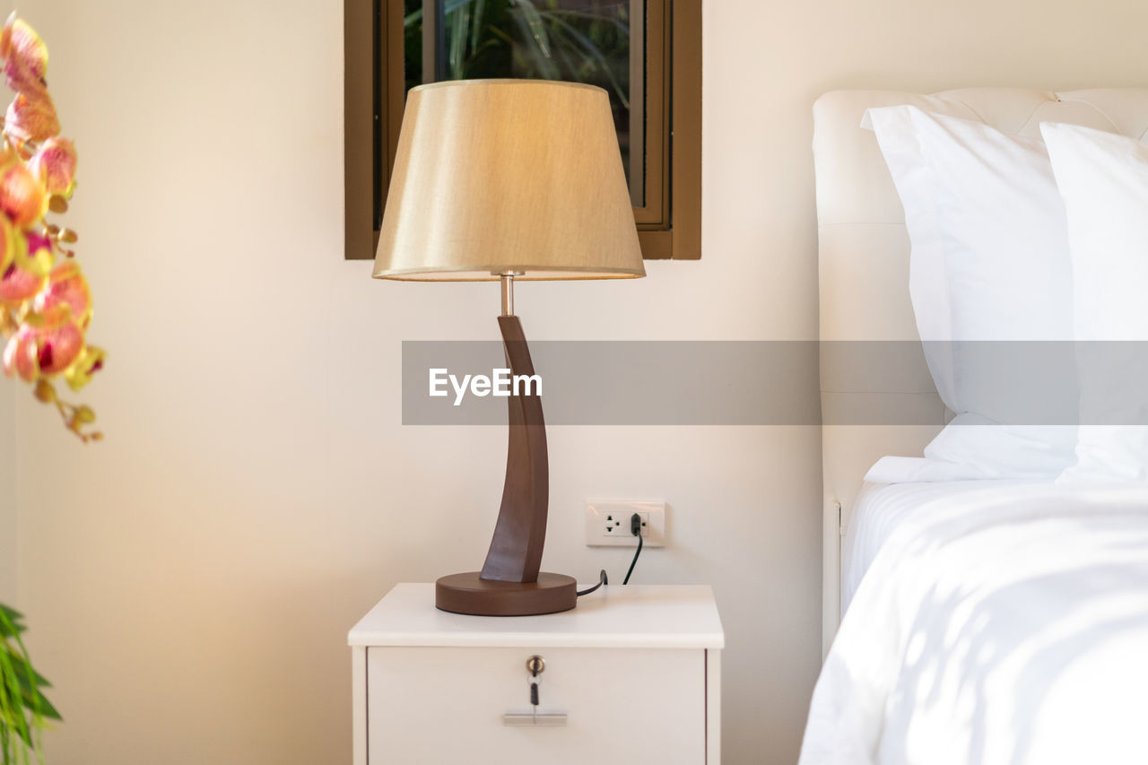 Electric lamp by bed in bedroom