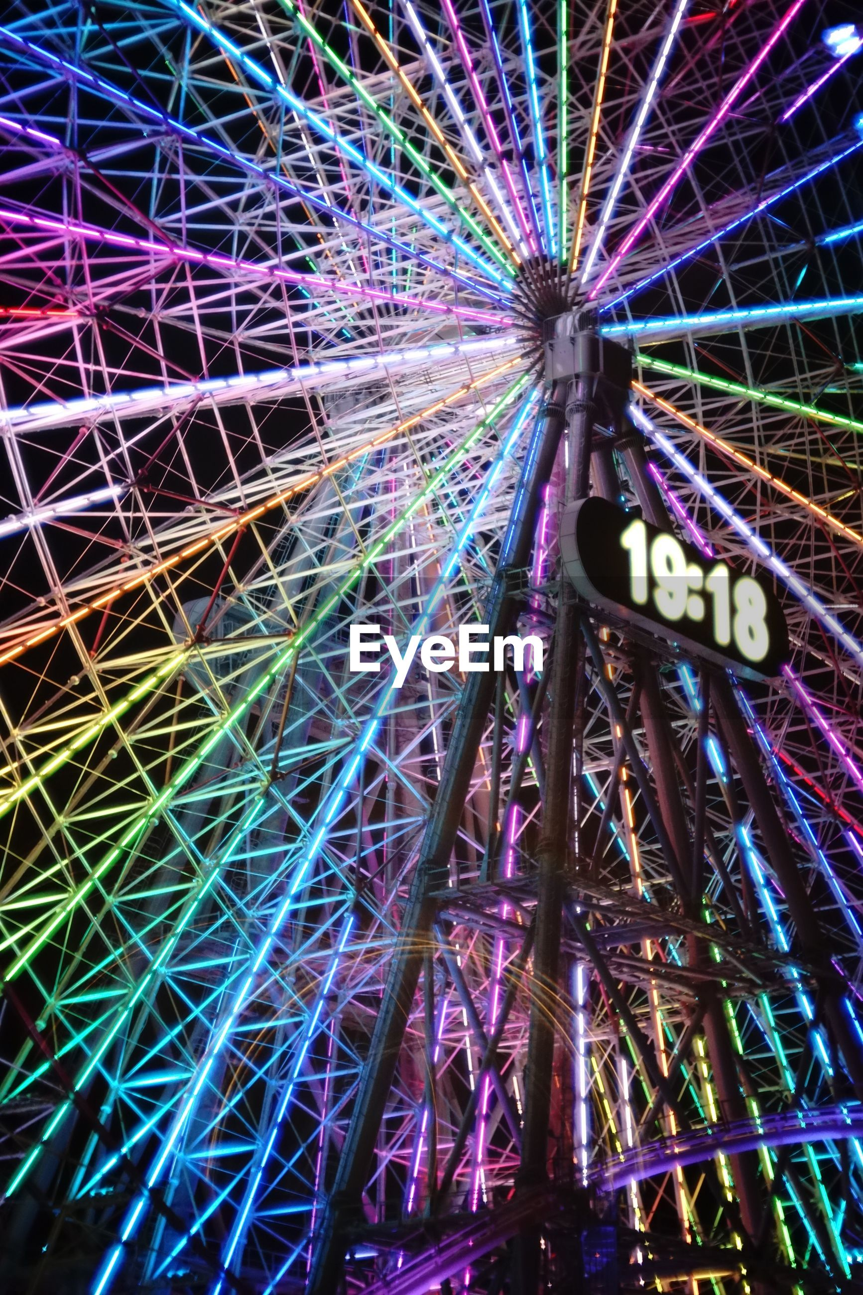 amusement park, low angle view, amusement park ride, arts culture and entertainment, ferris wheel, built structure, architecture, illuminated, metal, multi colored, night, outdoors, no people, sky, pattern, travel destinations, city, traveling carnival, metallic, motion
