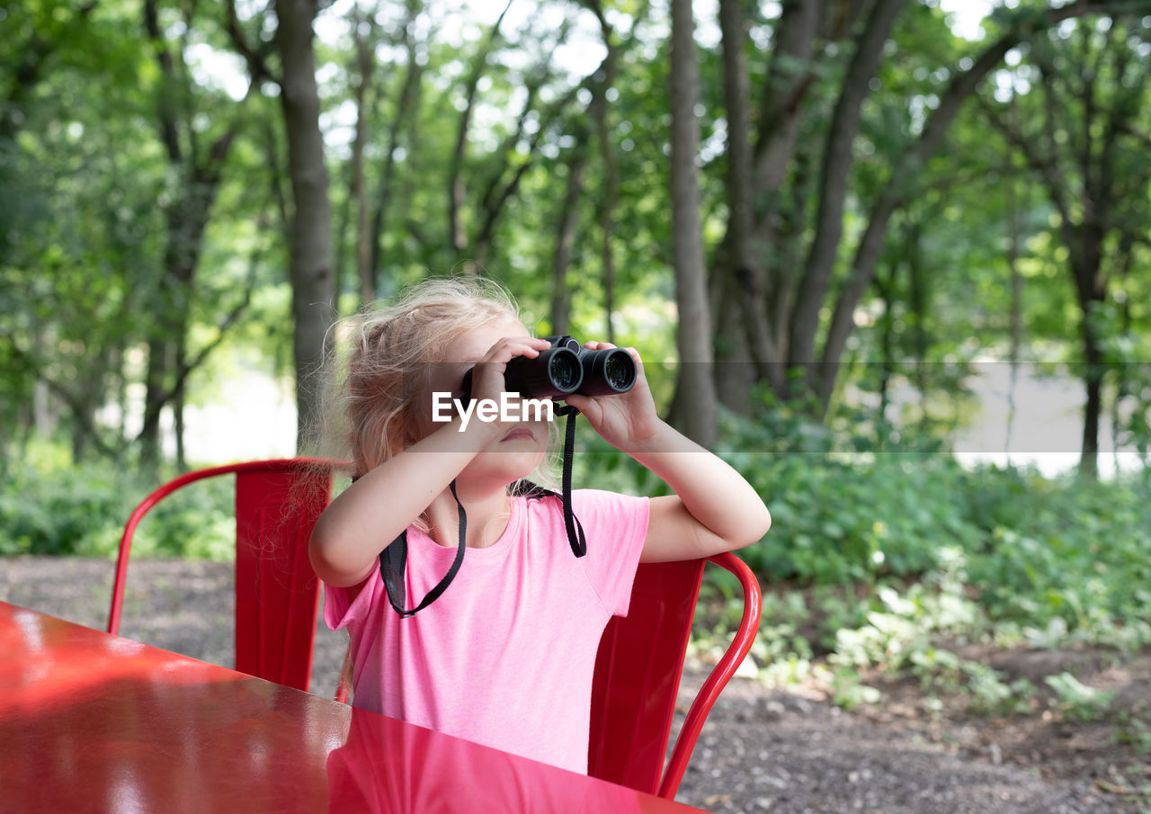 Close-up of girl looking through binoculars at table in forest