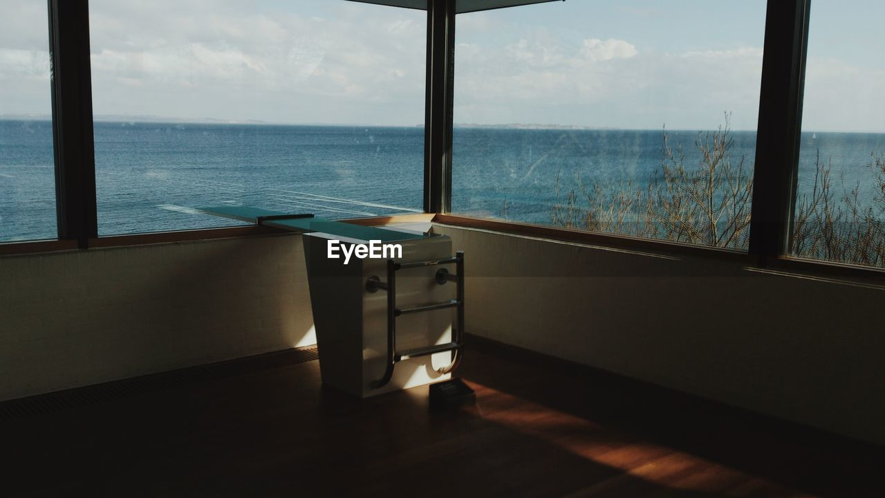 window, sea, water, indoors, nature, glass - material, transparent, horizon, day, table, no people, sky, sunlight, scenics - nature, horizon over water, beauty in nature, shadow, tranquility