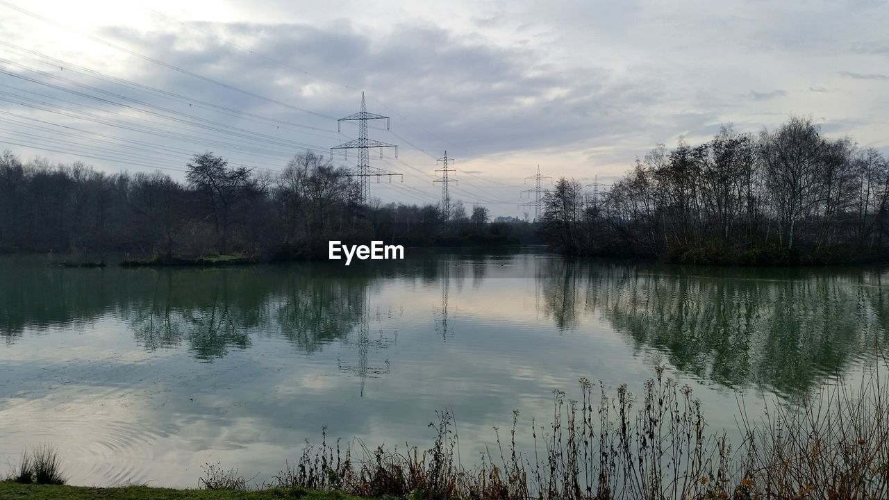 reflection, water, fuel and power generation, sky, cloud - sky, tree, tranquil scene, lake, nature, tranquility, electricity pylon, no people, outdoors, cable, electricity, power supply, beauty in nature, day, scenics, technology