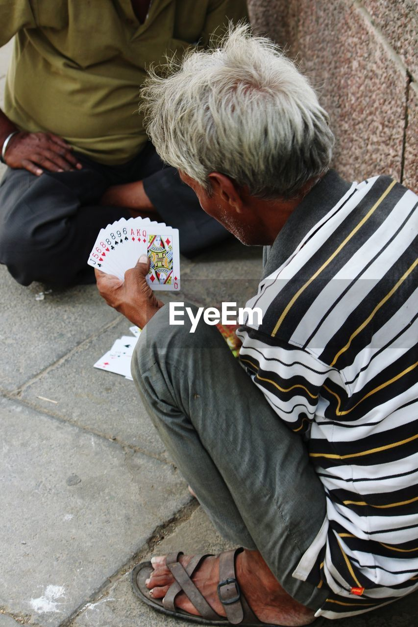High Angle View Of Men Playing Cards Outdoors