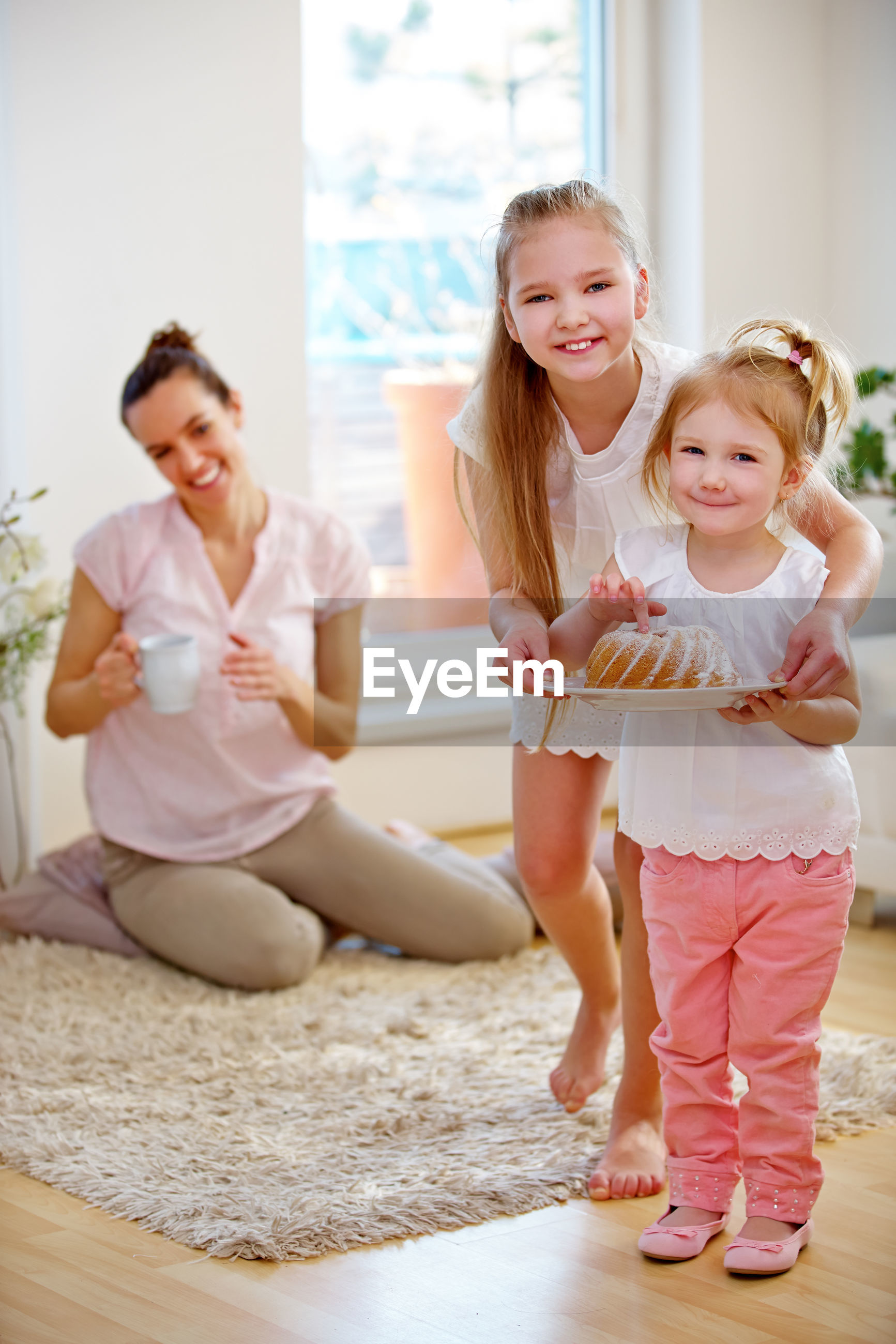 Laughing mother with daughters holding food at home