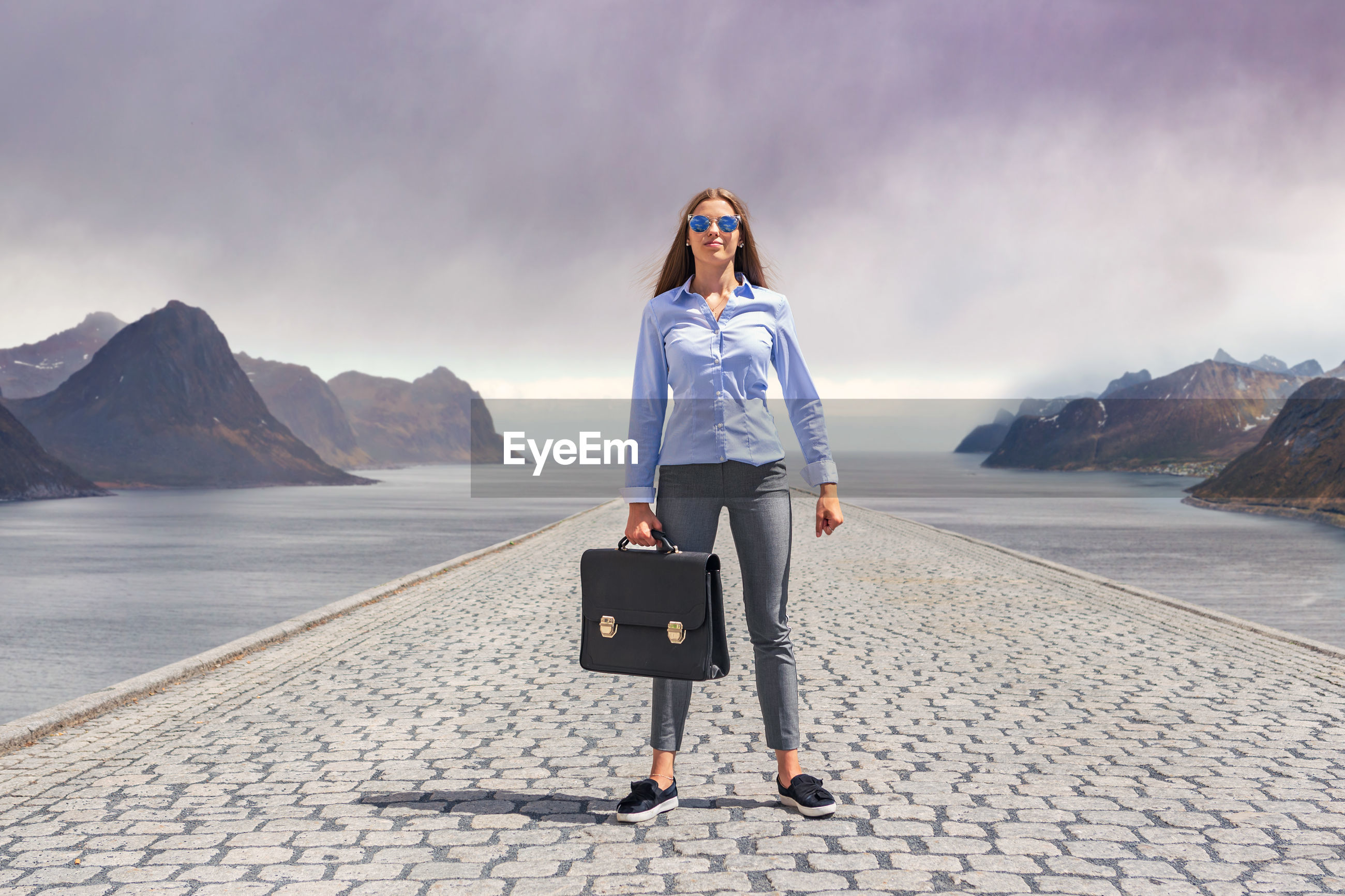 Portrait of young woman with briefcase standing on footpath amidst sea