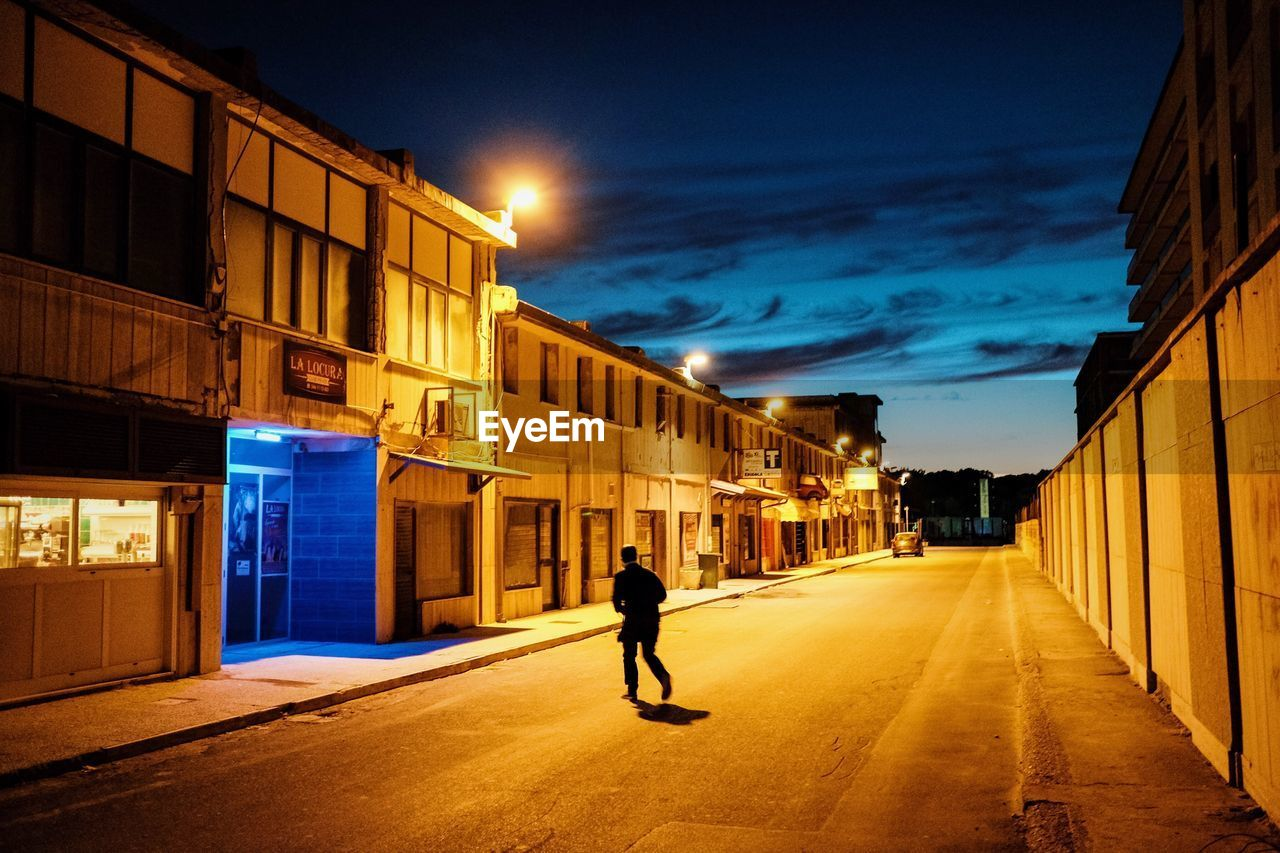 architecture, building exterior, built structure, illuminated, city, one person, direction, building, street, the way forward, sky, full length, night, real people, walking, lifestyles, nature, transportation, road, outdoors, diminishing perspective, alley