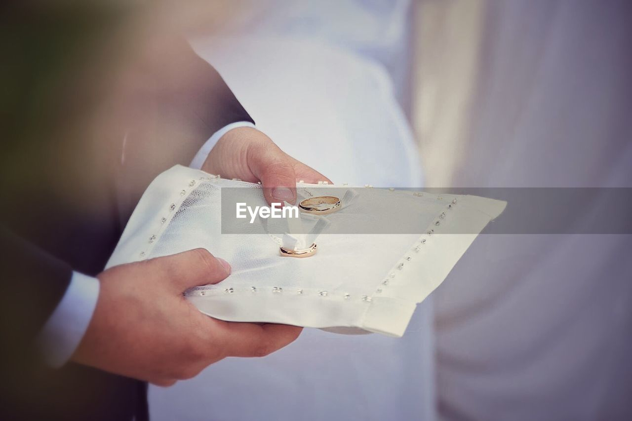 Cropped Image Of Man With Rings On Fabric During Wedding