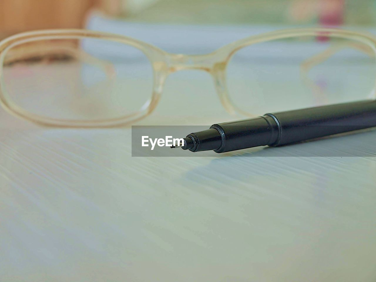 still life, pen, close-up, table, indoors, writing instrument, glasses, glass - material, selective focus, no people, eyeglasses, paper, transparent, focus on foreground, black color, single object, page, ballpoint pen, communication, fountain pen, surface level, personal accessory