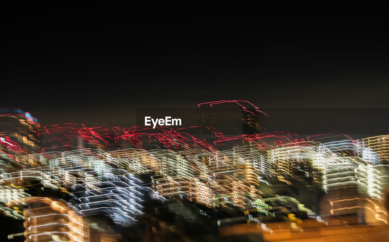 Low Angle View Of Light Trails Against Sky At Night