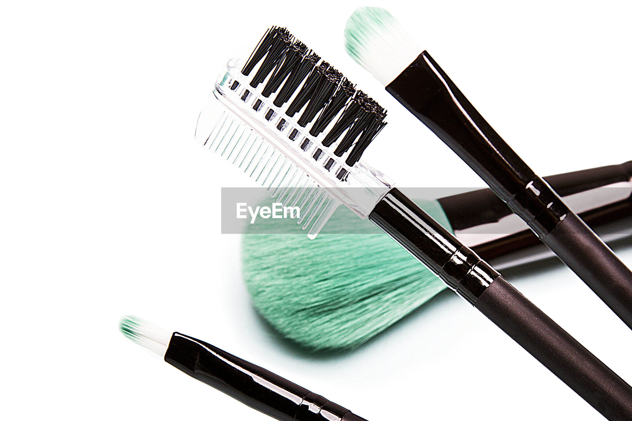 High angle view of make-up brushes against white background