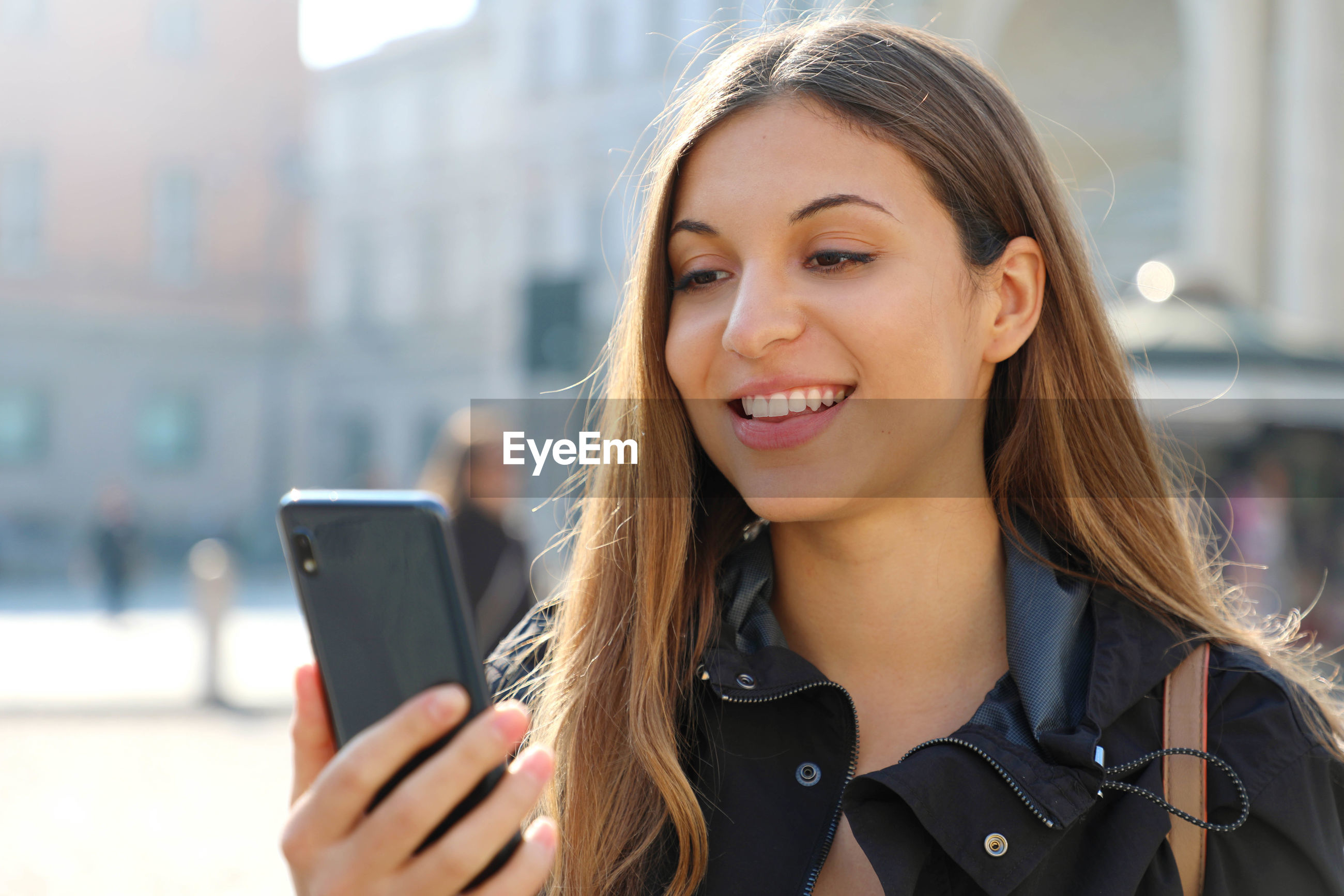 Smiling young woman using phone in city