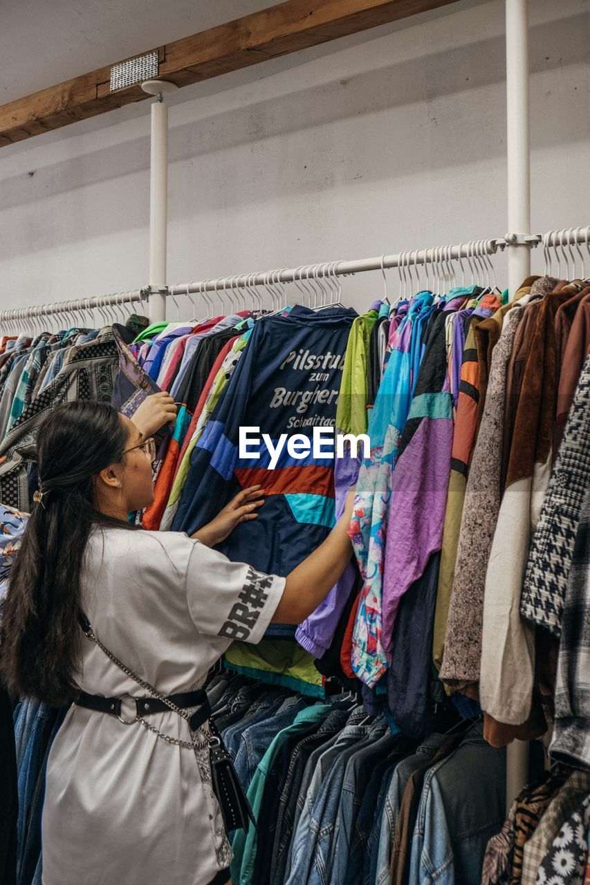 clothing, choice, variation, indoors, retail, rack, hanging, one person, multi colored, store, women, coathanger, shopping, clothes rack, business, waist up, adult, fashion, looking, decisions, sale, hairstyle, consumerism