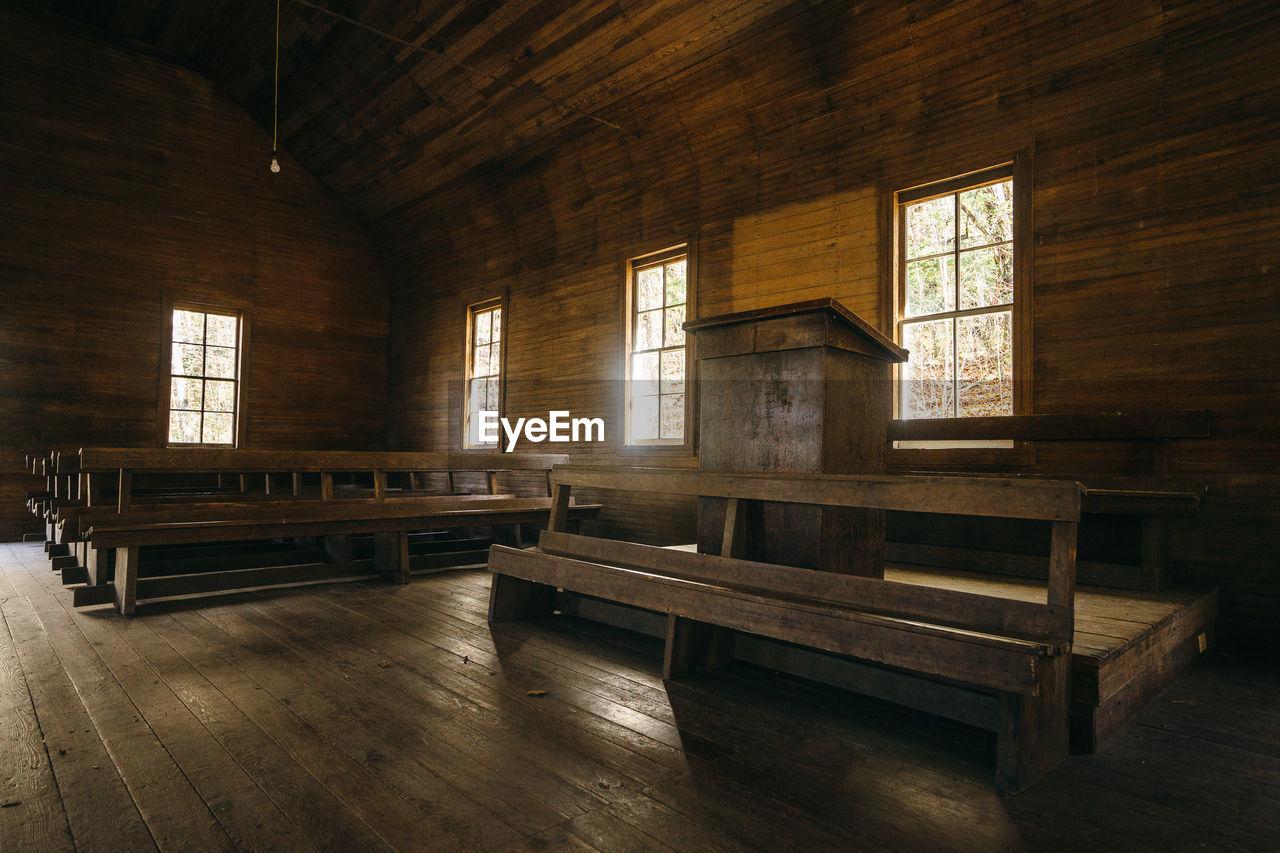 EMPTY BENCHES ON WOODEN FLOOR IN ROOM