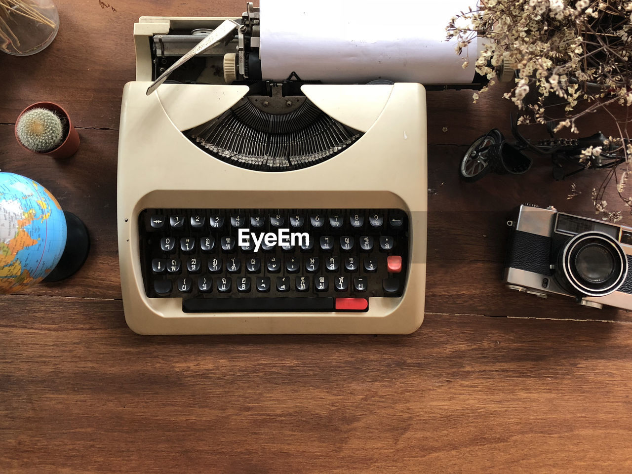 Directly Above View Of Typewriter With Camera And Decors On Wooden Table