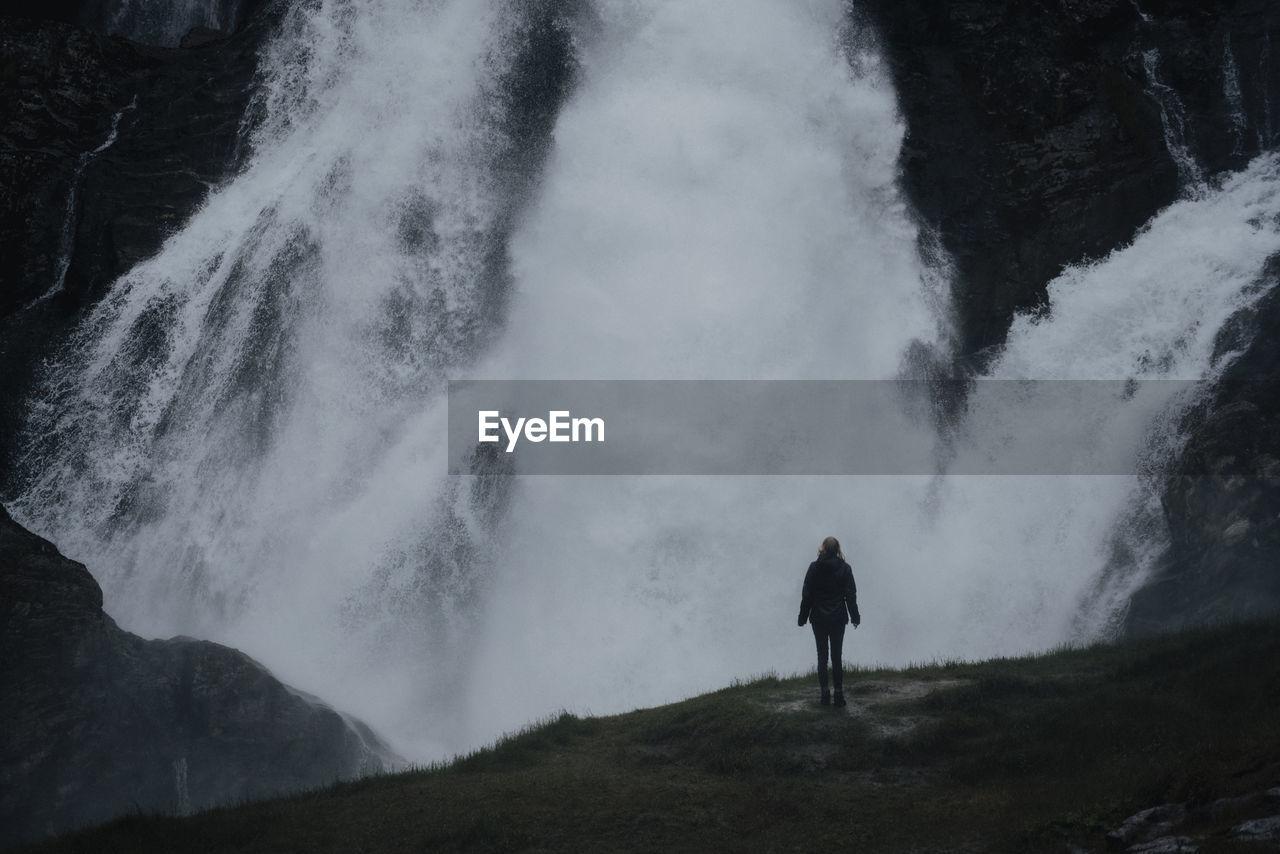 FULL LENGTH REAR VIEW OF MAN WALKING ON MOUNTAIN DURING WINTER
