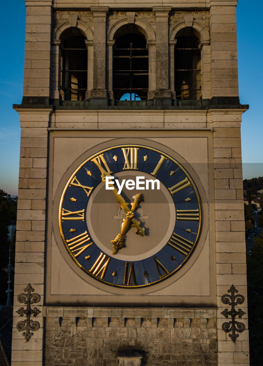 architecture, building exterior, built structure, window, time, clock, outdoors, clock tower, no people, day, roman numeral, clock face, history, low angle view, travel destinations, statue, minute hand, sky, close-up