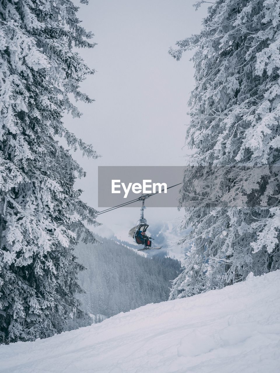 Low Angle View Of People On Ski Lift Over Snowcapped Mountain Against Sky