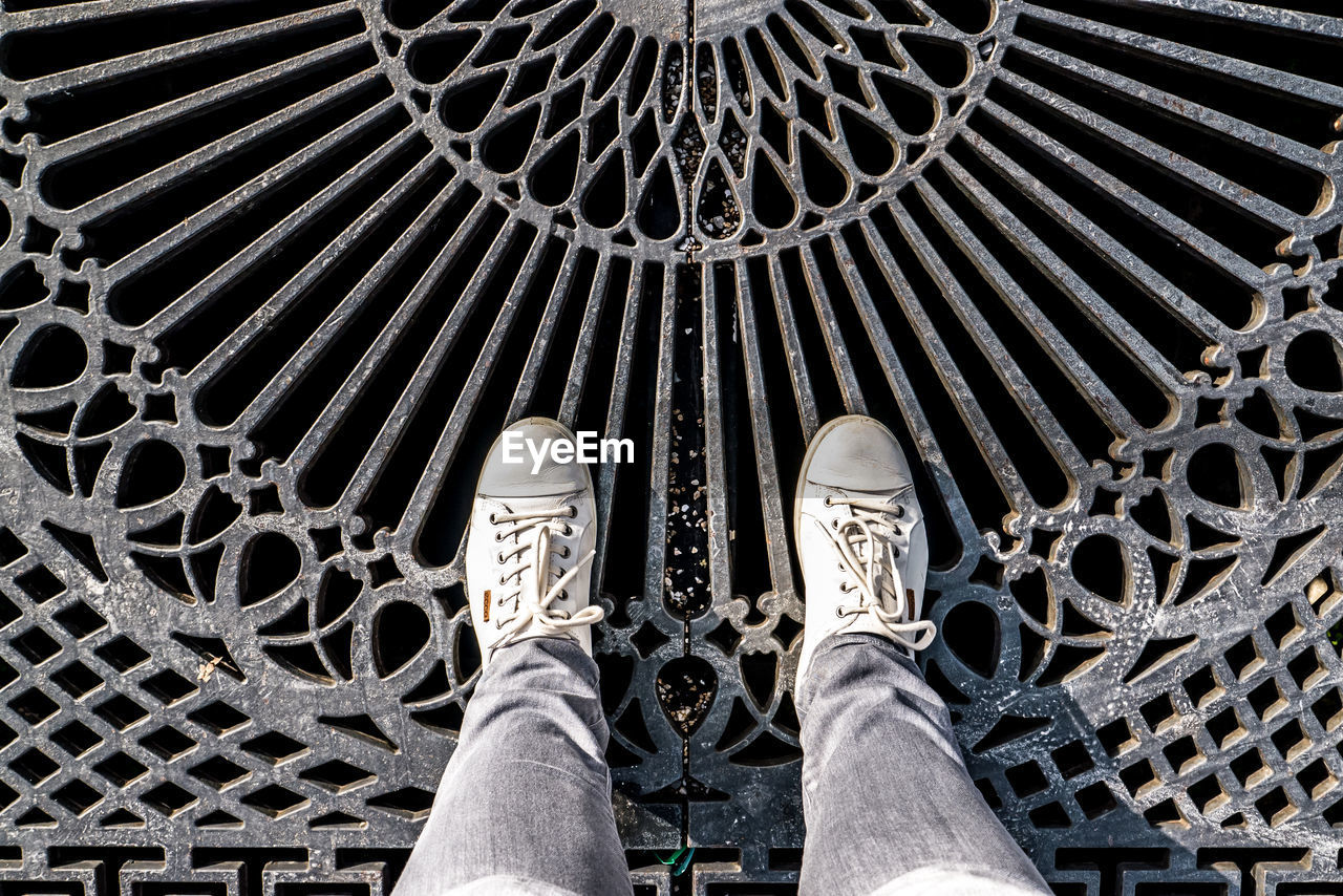low section, shoe, personal perspective, human leg, human body part, body part, one person, real people, pattern, standing, metal, lifestyles, unrecognizable person, men, day, leisure activity, human foot, high angle view, outdoors, jeans, sheet metal