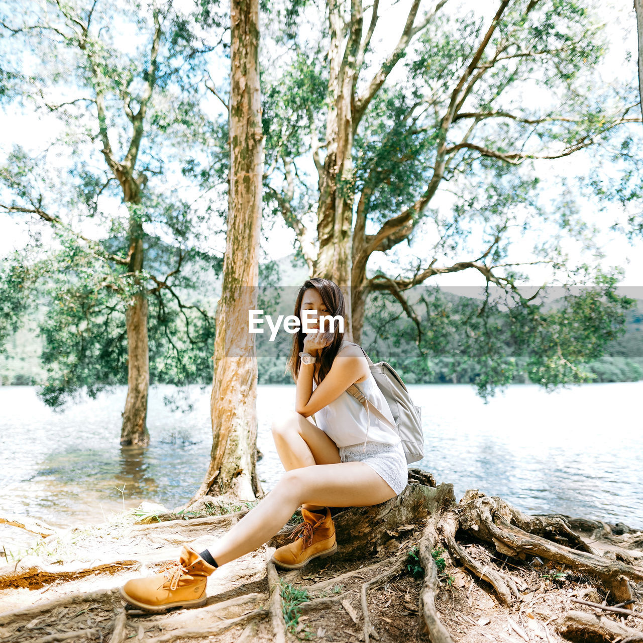 Young Woman Sitting On Lakeshore