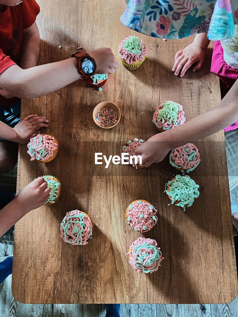 Group of children baking cupcakes, preparing ingredients, topping, sprinkles for decorating cookies