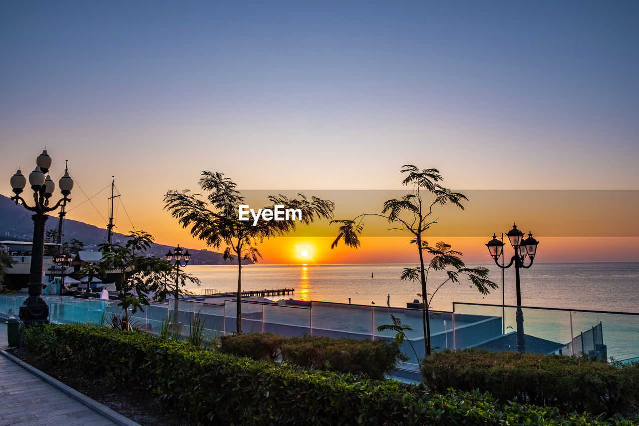 sky, sunset, water, sea, plant, tree, scenics - nature, beauty in nature, horizon over water, nature, horizon, tranquil scene, sun, tranquility, palm tree, tropical climate, beach, orange color, no people, outdoors, swimming pool, coconut palm tree
