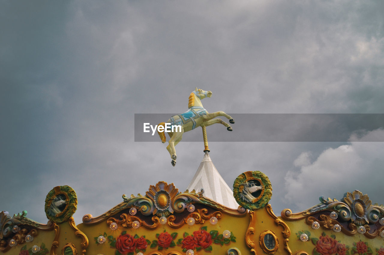 cloud - sky, representation, art and craft, sky, sculpture, low angle view, amusement park, statue, creativity, arts culture and entertainment, no people, human representation, day, nature, carousel, amusement park ride, overcast, architecture, outdoors, ornate