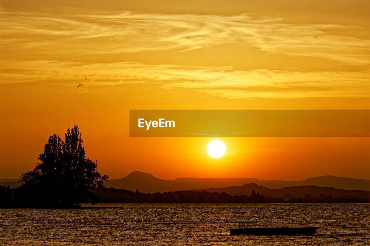 sunset, sky, beauty in nature, orange color, scenics - nature, water, tranquil scene, tranquility, sun, mountain, cloud - sky, idyllic, silhouette, nature, no people, yellow, mountain range, non-urban scene, sunlight, outdoors, romantic sky
