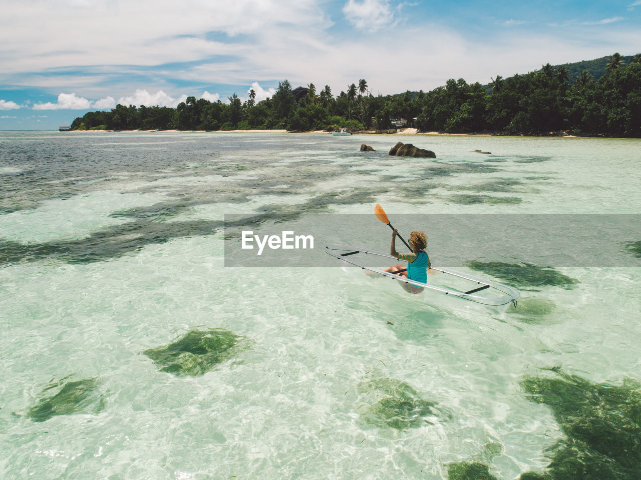 water, leisure activity, aquatic sport, one person, sport, sea, adventure, nautical vessel, waterfront, transportation, nature, kayak, motion, oar, day, lifestyles, extreme sports, sky, outdoors