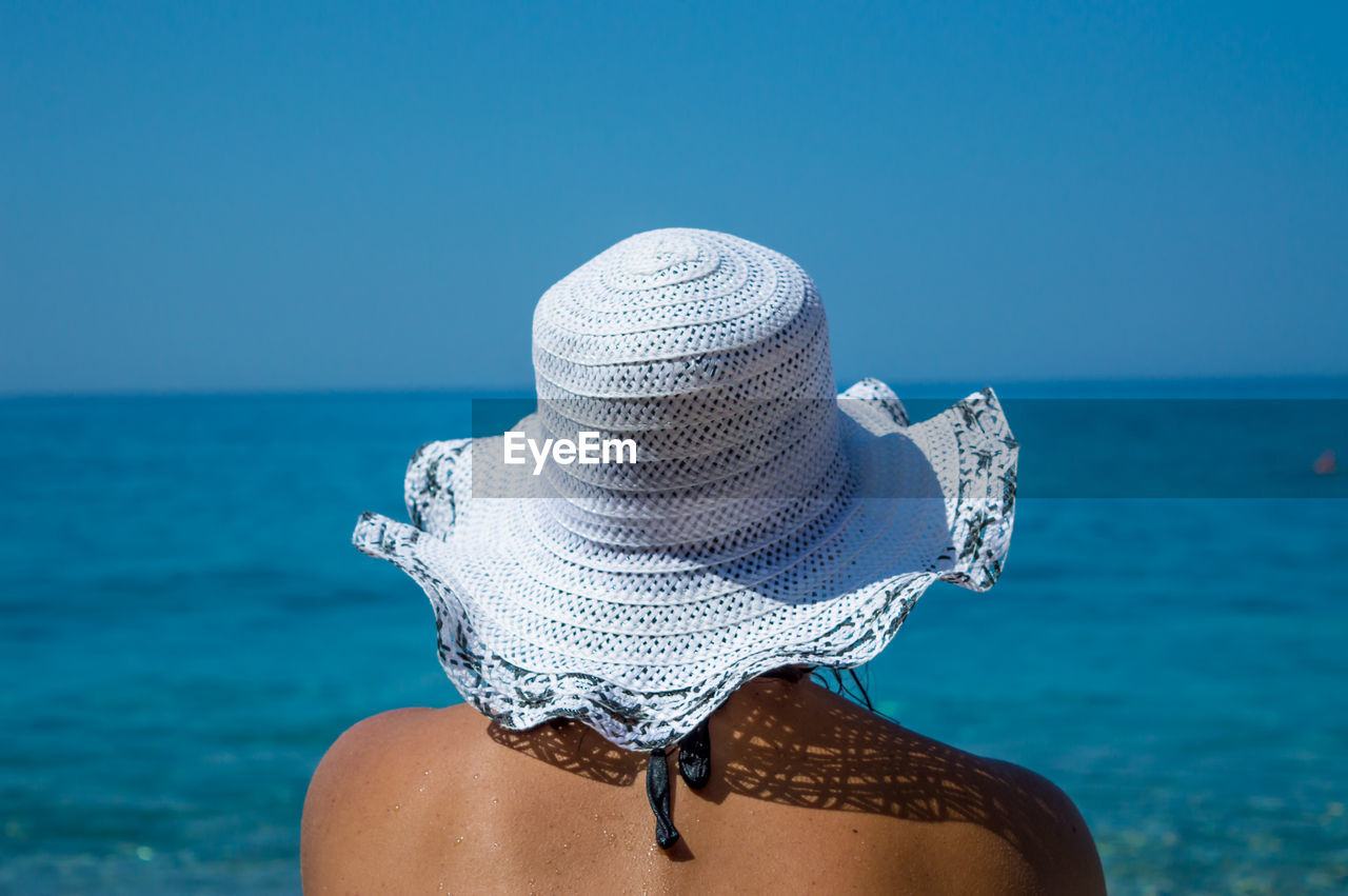 REAR VIEW OF WOMAN LOOKING AT THE OCEAN