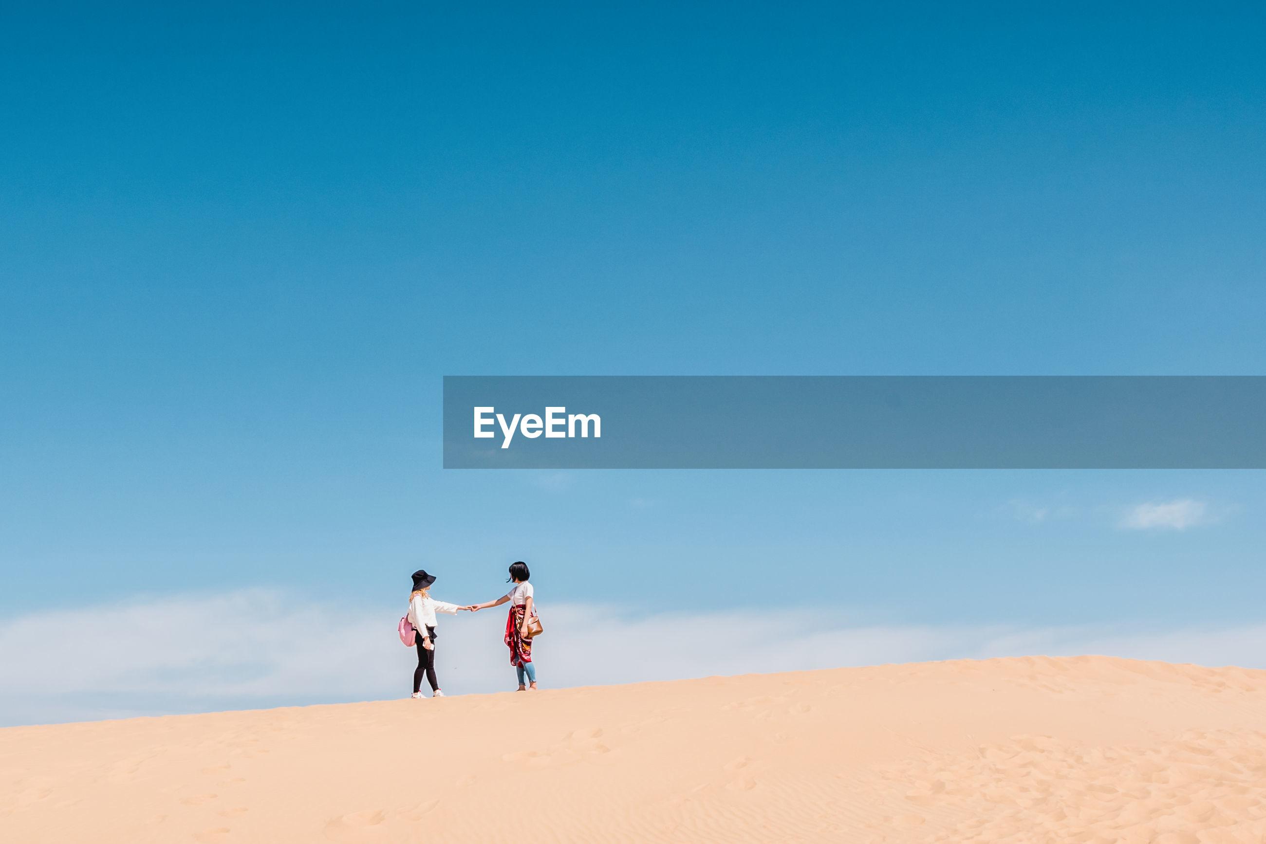 Friends standing in desert against sky