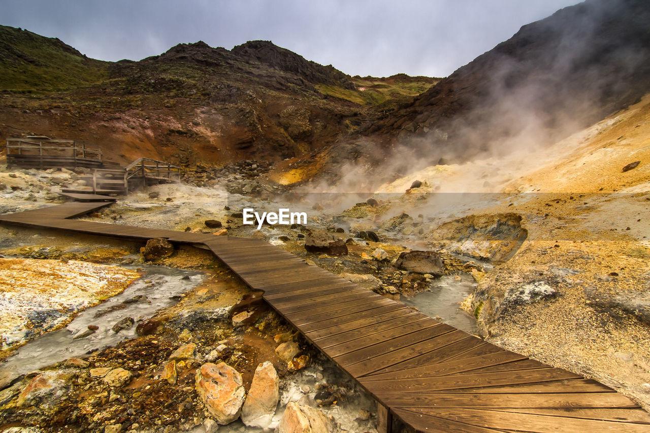 Boardwalk leading towards hot spring against sky