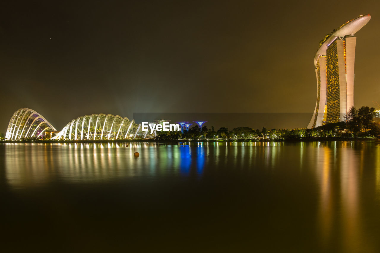Marina Bay Sands By Bay Of Water Against Sky In Illuminated City At Night