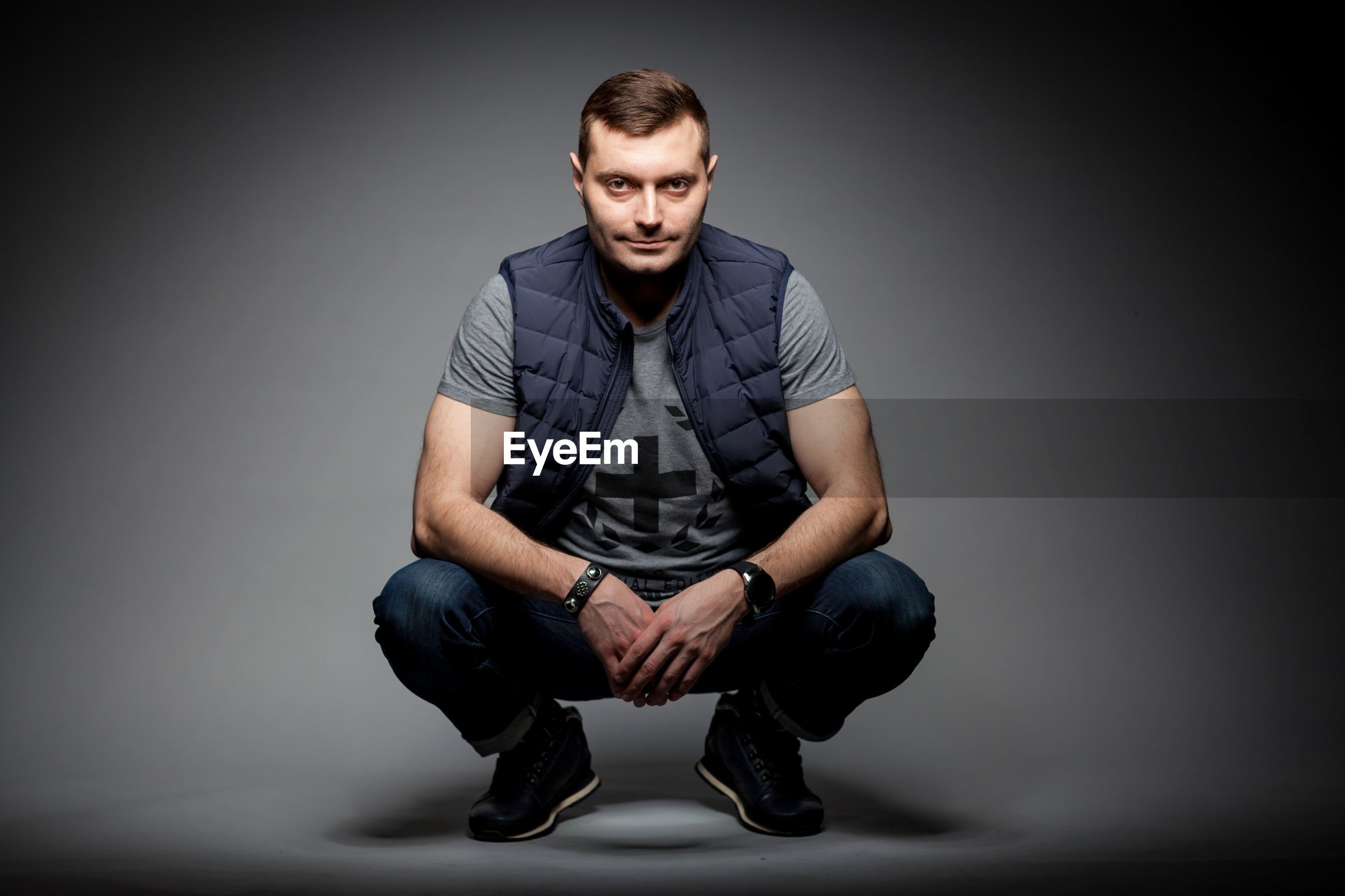 Fashionable mid adult man wearing jacket against gray background