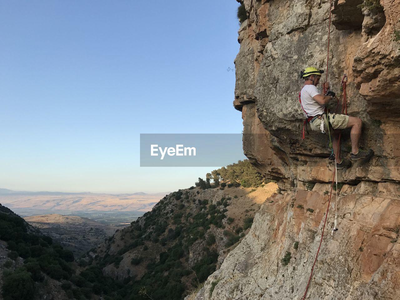 Man climbing on rock against clear sky
