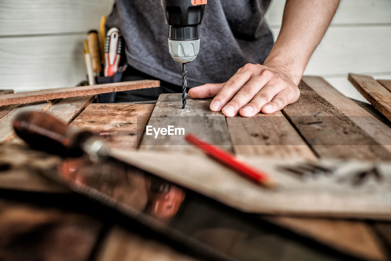 Midsection of male carpenter drilling wood in workshop