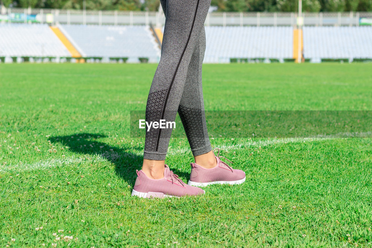 Low section of woman standing on playing field