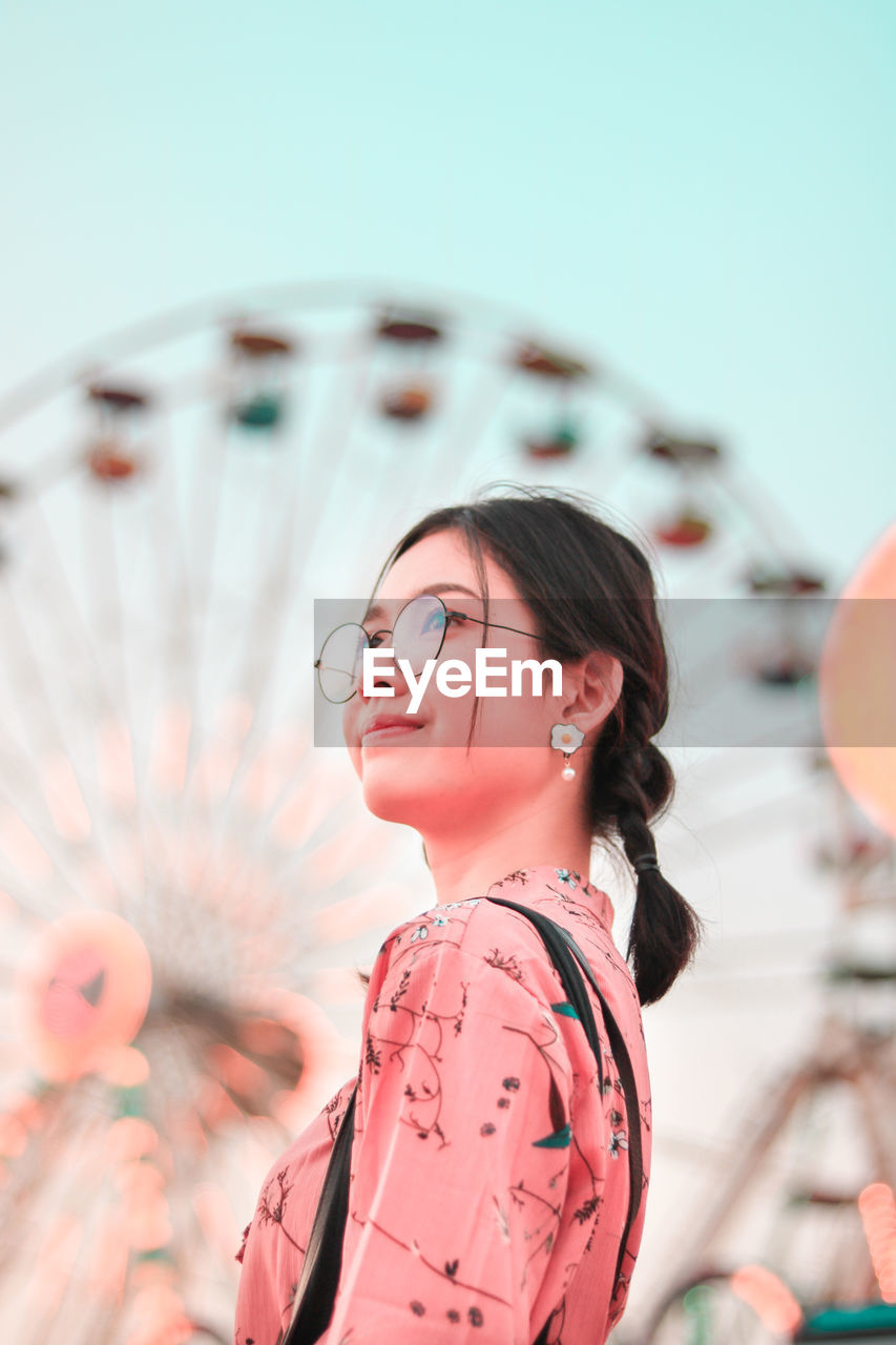 Young woman standing against ferris wheel