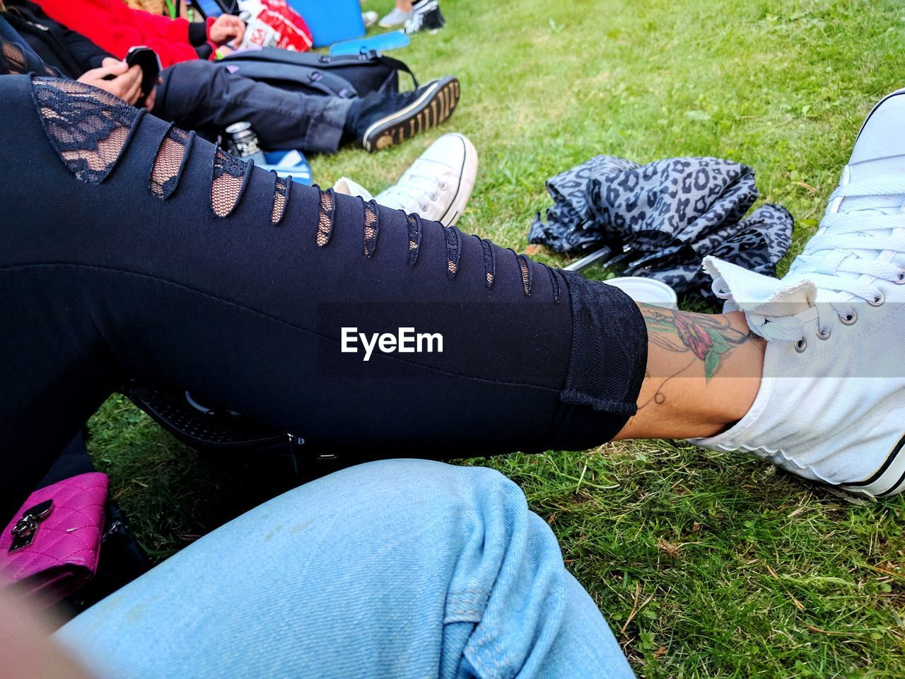 human leg, real people, low section, grass, day, outdoors, sitting, field, casual clothing, leisure activity, human body part, one person, lifestyles, men, human hand, close-up, adult, people