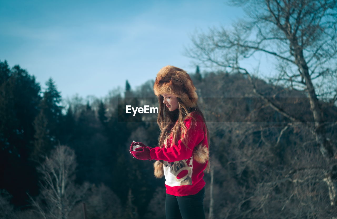 tree, one person, lifestyles, plant, real people, women, leisure activity, standing, hairstyle, nature, adult, clothing, day, females, long hair, hair, sky, three quarter length, outdoors, warm clothing