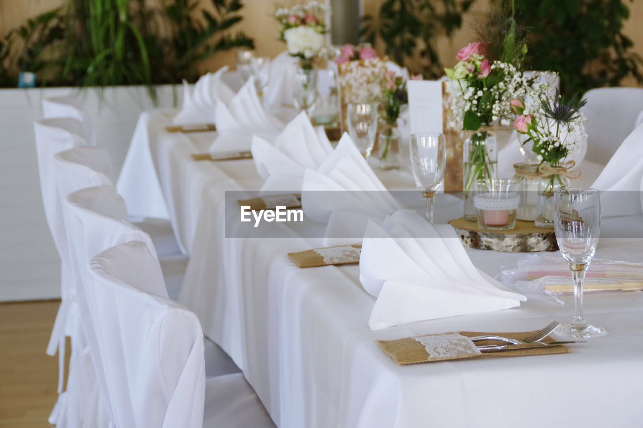 table, event, wedding, celebration, white color, furniture, place setting, setting, glass, plant, decoration, flower, chair, tablecloth, household equipment, flowering plant, no people, dining table, wineglass, wedding reception, wedding ceremony, bouquet, flower arrangement