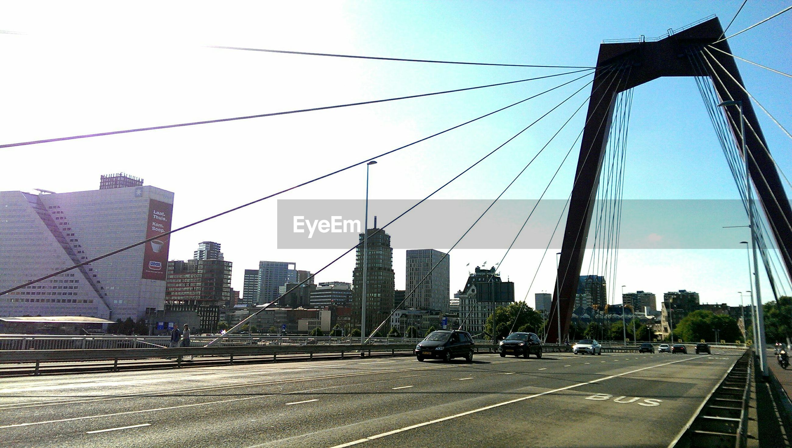 architecture, built structure, city, building exterior, transportation, skyscraper, road, clear sky, car, connection, cityscape, city life, bridge - man made structure, tower, modern, tall - high, street, sky, capital cities, office building