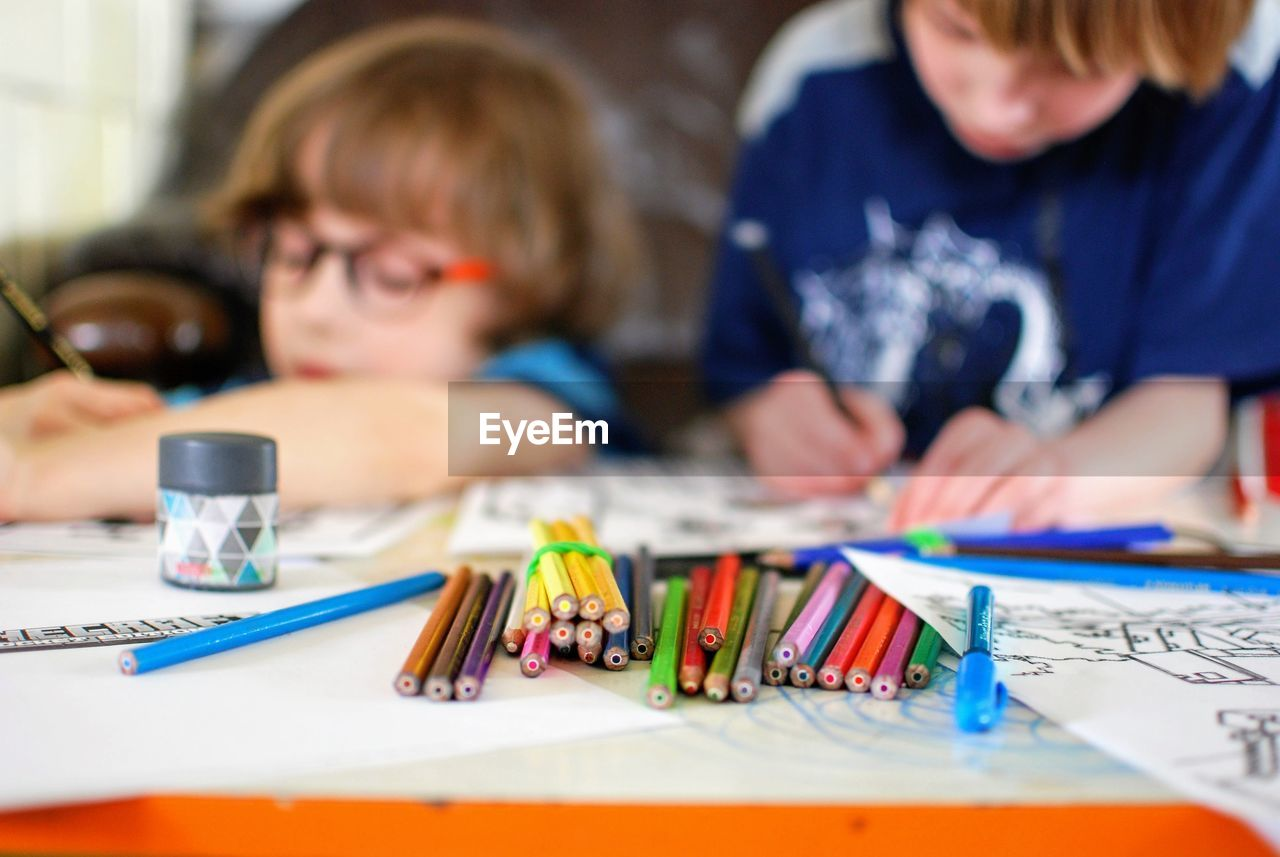 View Of Colored Pencils On Table With Boys Drawing In Background