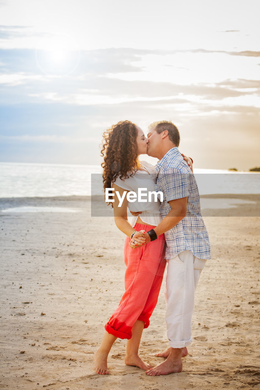 Couple Kissing While Standing At Beach Against Sky